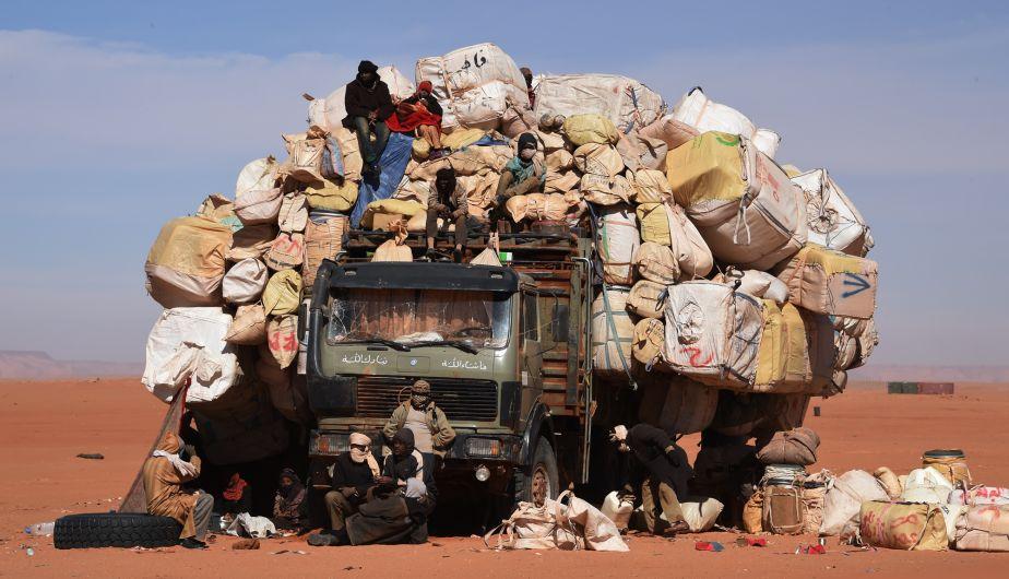 (1 de enero) Estas  personas se acomodan cerca de un camión cargado de todo tipo de contrabando. La imagen fue registrada en Madama, cerca de la frontera con Libia. (AFP)